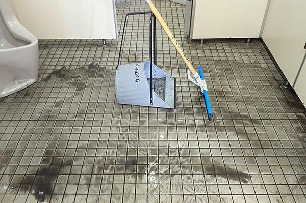 トイレ床清掃中 汚水の回収