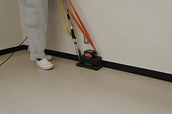 小型振動ポリッシャーにて壁際の床清掃中